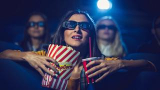 Woman in cinema with a drink and popcorn