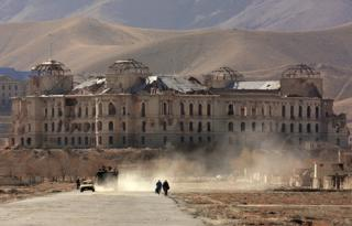 KABUL, AFGHANISTAN: Afghani people walk along a street in Kabul, with the ruined palace of former Afghani Prime Minister Hafizullo Amin in the background, 15 November 2001. Amin was killed in December 1979 in his palace by the officers of Soviet 'Alpha' special task unit, as a first action of Soviet 1979-1989 invasion to Afghanistan. The Northern Alliance opposition forces scored a crushing victory against Afghanistan's hardline Taliban regime 13 November evicting it from the capital Kabul and seizing control of a huge tract of surrounding territory.