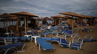 Сломанные пляжные зонтики и шезлонги