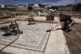 An archaeologist works on a mosaic near Vienne, south-eastern France, 31 July