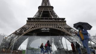A woman wearing a face mask passes by the Eiffel Tower, 14 March