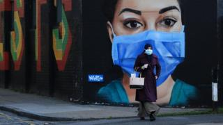 science A woman wearing a mask walks in front of a mural of an NHS worker