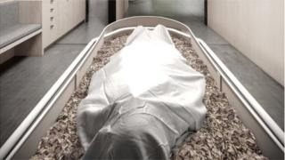 A body is seen covered by a sheet on a bed of woodchips