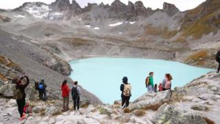 People look at the Pizol glacier as they take part in a mourning ceremony