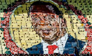 People display the portrait of Zimbabwe's President Emmerson Mnangagwa during Independence Day celebrations at the National Sports Stadium on April 18, 2018 in Harare. Zimbabwe on April 18 marked its first independence day without Robert Mugabe in power, with new leader Emmerson Mnangagwa vowing to hold 'credible' elections and turn around the southern African country's moribund economy.