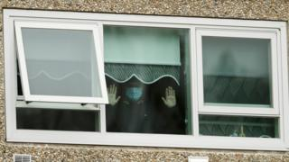 in_pictures A man wearing a mask holds his hands up to the window in one of the housing towers