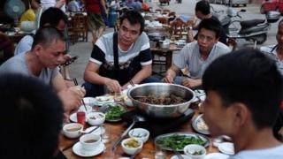 Homens comendo em festival que vende carnes de cachorro na China