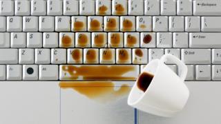 Una taza de café derramada sobre un teclado