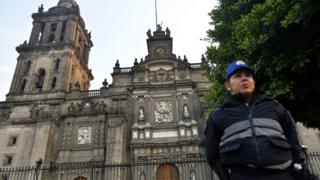Una mujer policía frente a la entrada de la catedral metropolitana de Ciudad de México.