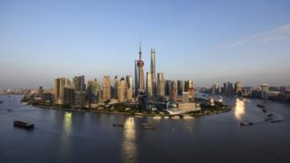 Ships pass by the skyline of the Lujiazui Financial District in Pudong in Shanghai