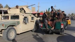 Milita fighters sit with their guns in the back of a truck passing an armed vehicle in Kunduz