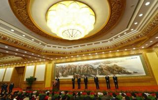 The Communist Party of China's new Politburo Standing Committee, the nation's top decision-making body, (L-R) Zhang Gaoli, Liu Yunshan, Zhang Dejiang, Li Keqiang, Yu Zhengsheng and Wang Qishan listen as Vice President Xi Jinping (L) delivers his address as they meet the press at the Great Hall of the People in Beijing on 15 November 2012