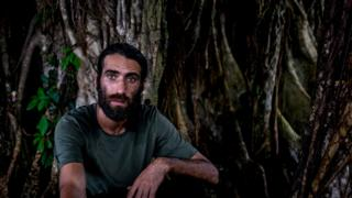 Behrouz Boochani sits under a tree on Manus Island