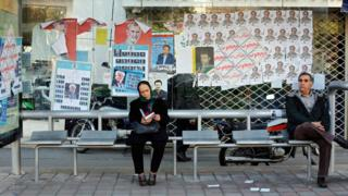 People sit at a bus stop covered in election posters in Tehran, Iran (25 February 2016)