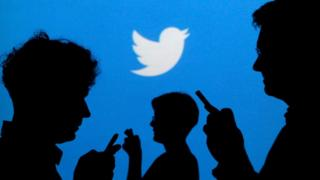 People using Twitter in silhouette