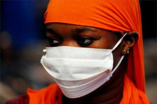 in_pictures A woman wears a white face mask and covers her hair with an orange fabric.