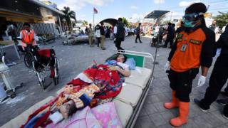 An injured quake victim waits for medical help outside the Moh. Ruslan hospital in Mataram on the Indonesian island of Lombok
