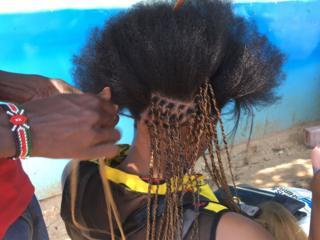 A woman gets her hair braided