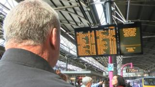 Mr Frank looking at a train information board