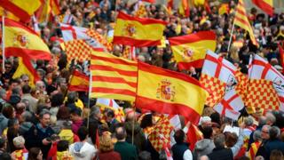 "People hold Spanish and ""Tabarnian"" flags during a pro-unity rally organised by the Tabarnia movement, a fictional region that wants independence from Catalonia, on 4 March 2018 in Barcelona"