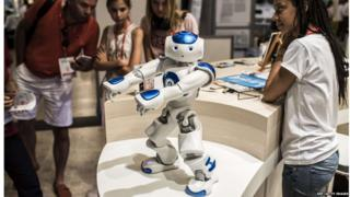 Visitors look a humanoid robot at Innorobo Europe's biggest robotics exhibition.