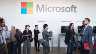 Peopel walk past a Microsoft sign