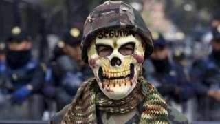 Hombre protesta contra la ley para regularizar la presencia militar en las calles mexicanas.