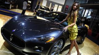 A model poses next to a Maserati at Auto Shanghai 2009