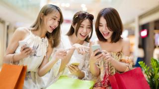 Young women launghing at smartphones