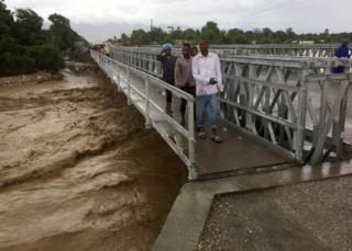 People cross a bridge while Hurricane Matthew passes in Port-au-Prince, Haiti, on October 4, 2016.