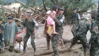 Soldado rescata a una niña de los escombros.