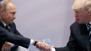 Vladimir Putin shaking hands with Donald Trump