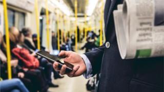 Pessoa olhando o celular no metrô