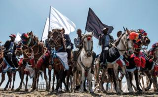 in_pictures Horsemen hold black and white flags during a memorial ceremony at the crash site of the Ethiopian Airlines Flight 302 in Tulu Fara, Ethiopia - Sunday 8 March 2020