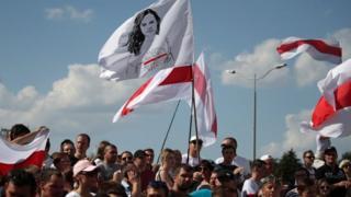 Activistas de la oposición de Bielorrusia sostienen una bandera con un retrato de la líder de la oposición Svetlana Tikhanovskaya