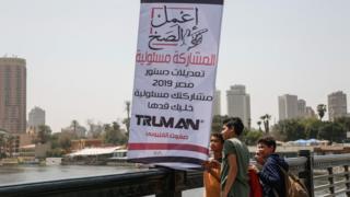 أطفال يتفقدون لافتة دعائية للمشاركة في الاستفتاء على التعديلات الدستورية