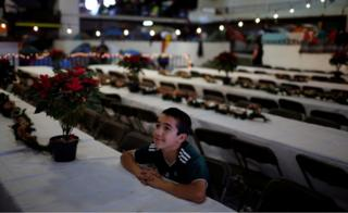 A migrant, part of a caravan of thousands from Central America trying to reach the United States, celebrates Christmas, at a temporary shelter in Tijuana, Mexico
