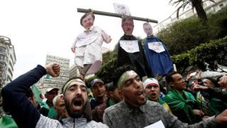 متظاهرون يحملون صور لمسؤولين جزائريين في المشنقة