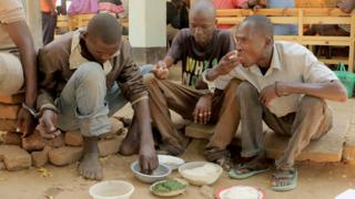 Handcuffed men eating food in the courtyard of a magistrate's court in Nsanje, Malawi - Monday 15 August 2016