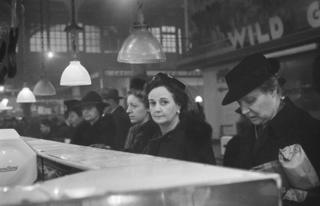 Customers waiting in line at a butcher's counter during wartime rationing. Washington Market, New York, 1941-44