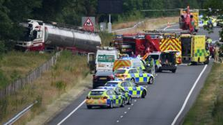 Scene of the crash with a lorry in a ditch and several emergency service vehicles, including an air ambulance, on the road