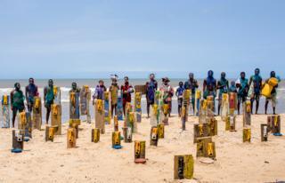 People standing near artwork using jerrycans by artist Serge Attukwei Clottey on a beach in Accra, Ghana