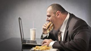 man eating over computer