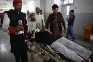Pakistani medics move an injured security personnel for a treatment at a hospital in Peshawar on February 15, 2017