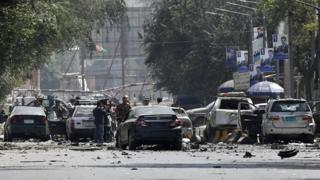 Afghan security forces inspect the scene after a suicide attack targeted a checkpoint in downtown Kabul