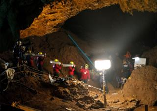 Thai officials carry oxygen tanks through a cave complex at the Tham Luang cave