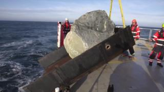 Boulder tipping into the sea
