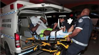 An injured inmate is carried on a stretcher into a hospital by police paramedics after a shootout among inmates at La Joyita prison, in Panama City, Panama December 17, 2019