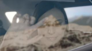 Woman traces landscape on car window