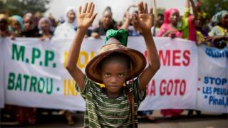 "A Fulani boy protests in front of a sign saying ""Stop the Genocide"" during a silent march orhanized by the Mouvement Peul et allies pour la paix, an organisation of ethnic Fulani people on June 30, 2018 in Bamako in response to a massacre in Koumaga, Mali. On June 23, at least 300 Christian farmers were killed and ten are missing following an attack in central Mali, believed to have been carried out by Muslim Fulani hunters"